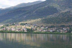 Конусообразные горы как в зеркале отражаются в водах озера Памвотида