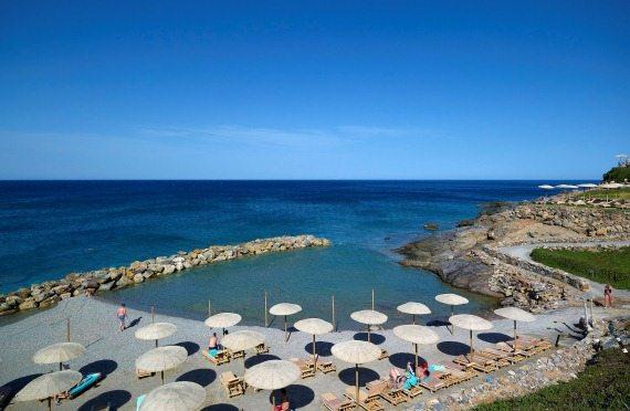 Пляж отеля выполнен в виде небольшой бухты, отделенной от моря волнорезом
